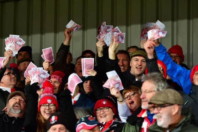 Gloucester fans waving fake money and wearing caps during the Gallagher Premiership match against Saracens