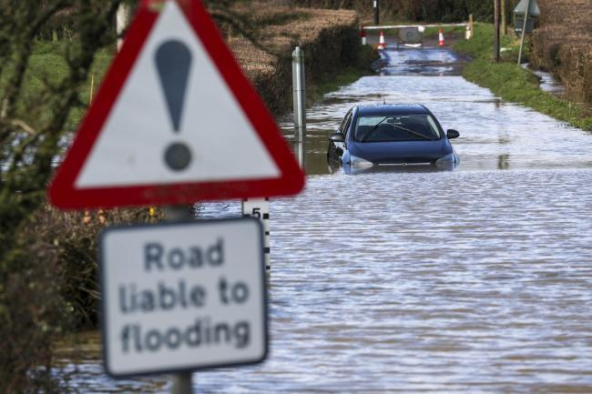 A car on a flooded road with a 'road liable to flooding' sign
