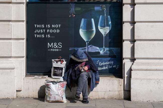 A homeless man sits outside a Marks and Spencer in Mayfair, London as the Government has asked local authorities in England to house all rough sleepers and those in hostels and night shelters by the weekend, the charity Crisis said. Image: Aaron Chown/PA