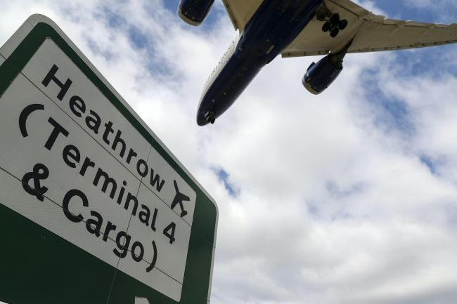 Plane flies over one of Heathrow's two runways