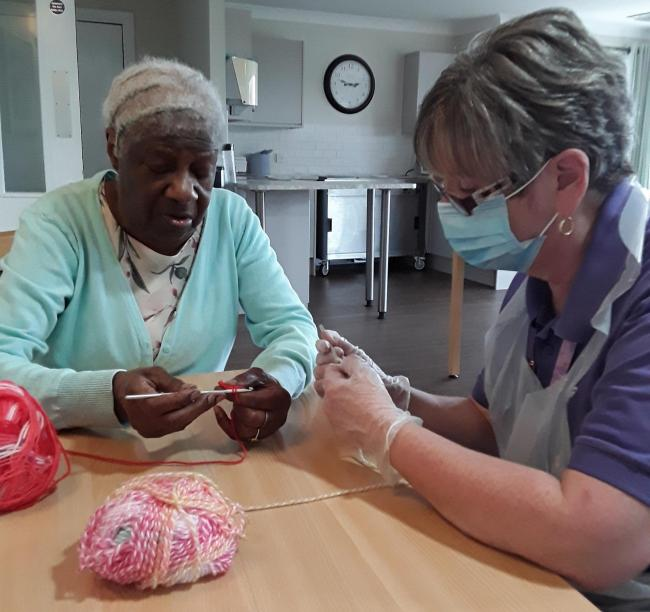 Whitefarm Lodge resident Gaona teaching Lifestyle team Linda McGuire how to crochet