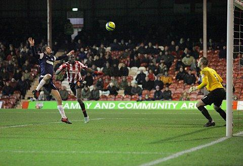On target: Clayton Donaldson gets up to head towards goal only to find former Bees keeper Paul Smith in fine form on Tuesday