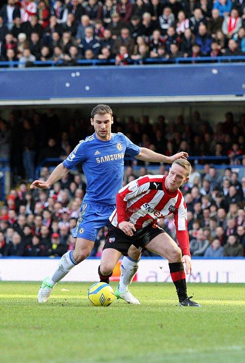 Looking up: Adam Forshaw feels the force of Chelsea defender Branislav Ivanovic on Sunday