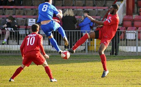 No fear: Ola Sogbanmu puts in the tackle despite the high-flying antics of Bury Town's Craig Parker     SP73061