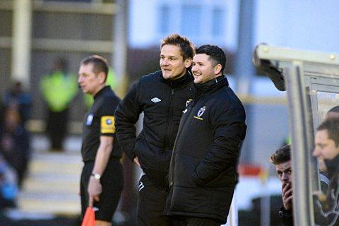 Happy family: Neal Ardley and Simon Bassey share a joke on the touchline    SP72885