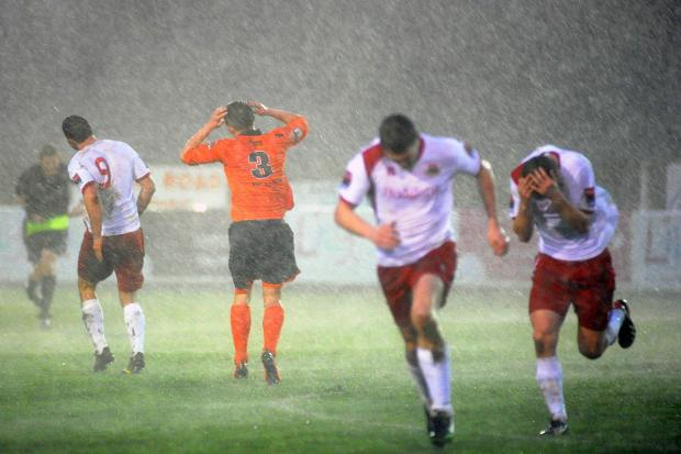 Run for it: Whitstable Town players run for cover during the storm that forced the abandonment of Saturday's game