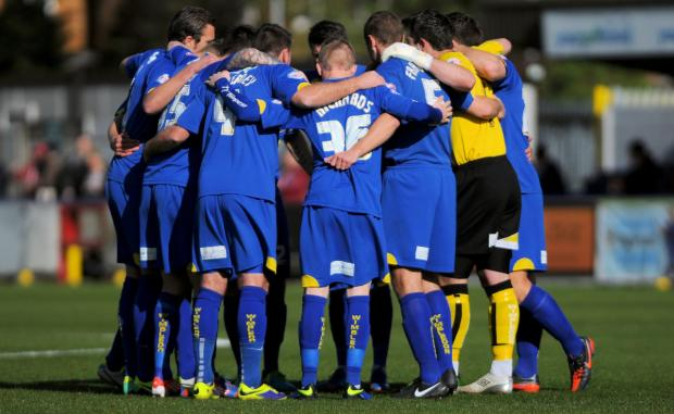 We're all friends here: The Dons lads get into the huddle prior to the win over Cheltenham