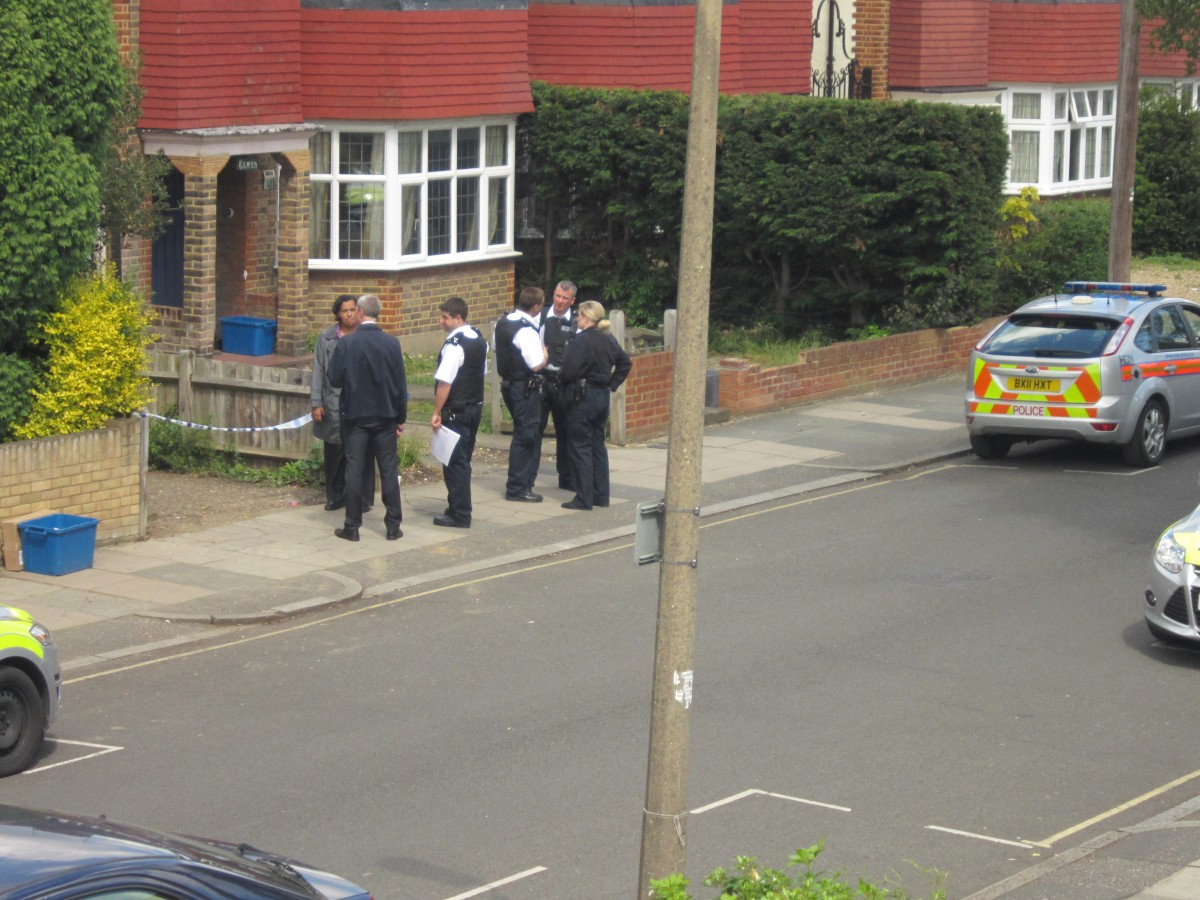 Scene: Officers near the site of the stabbing this afternoon